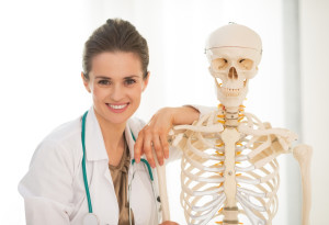 Portrait of smiling medical doctor woman near human skeleton anatomical model