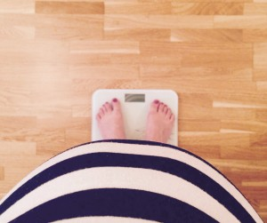 Pregnant woman measuring weight