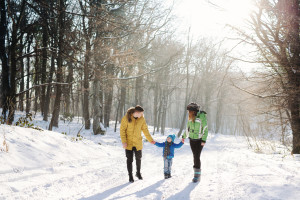 Little boy enjoying playing with his young mom and dad. Toddler kid holding hands with parents. Children play outdoors in snow. Kids sled in winter park. Outdoor active fun for family vacation.